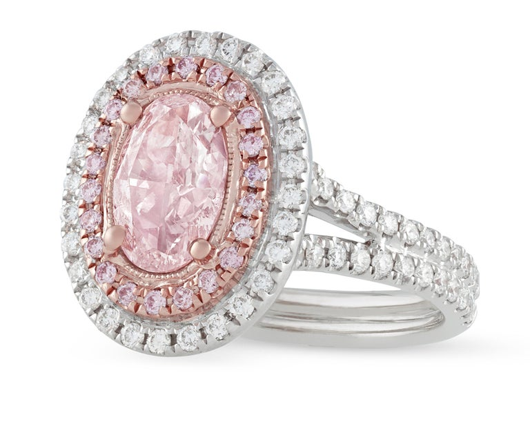 Displaying a delicate, even coloration is the beautiful natural fancy light pink diamond in this ring. Certified by the Gemological Institute of America to be natural fancy light brown-pink, this fabulous 1.30-carat diamond is surrounded by a halo