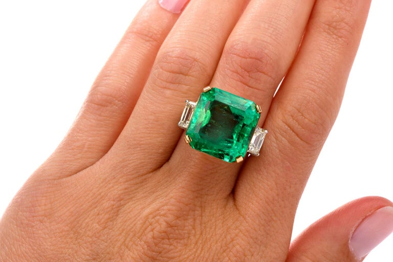This stately Emerald and Diamond Cocktail Engagement ring was inspired in   a traditional 3 stone design and crafted in Platum and 18K yellow gold.  Prominent in the center is an Octagonal Shpaed Natural GIA certified Emerald  measuring appx. 16.42