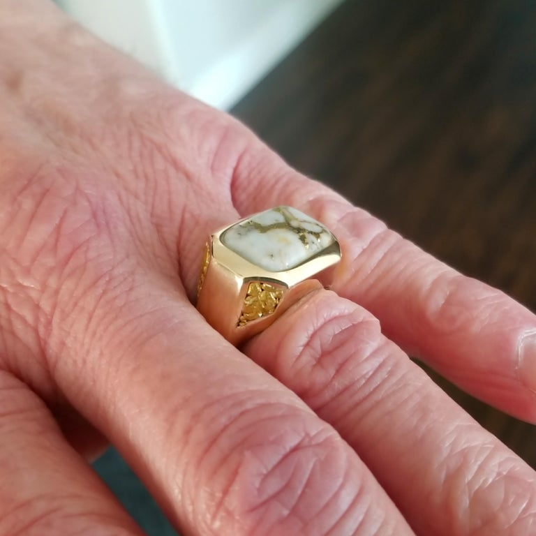 Exquisitely rare natural gold bearing quartz and gold nuggets are the focal points of this elegant and unique men's ring. The classic shape and styling are a perfect frame for the natural material choices, and the vivid color of the two types of