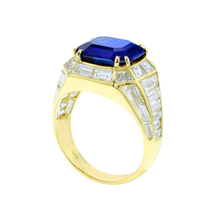A chic sapphire and diamond ring, centered with an approximately five carat, natural no-heat rectangular step-cut Burma Sapphire, accented with a single row of tapered baguettes, flowing towards the shoulders and tapered sides; stamped 750. The