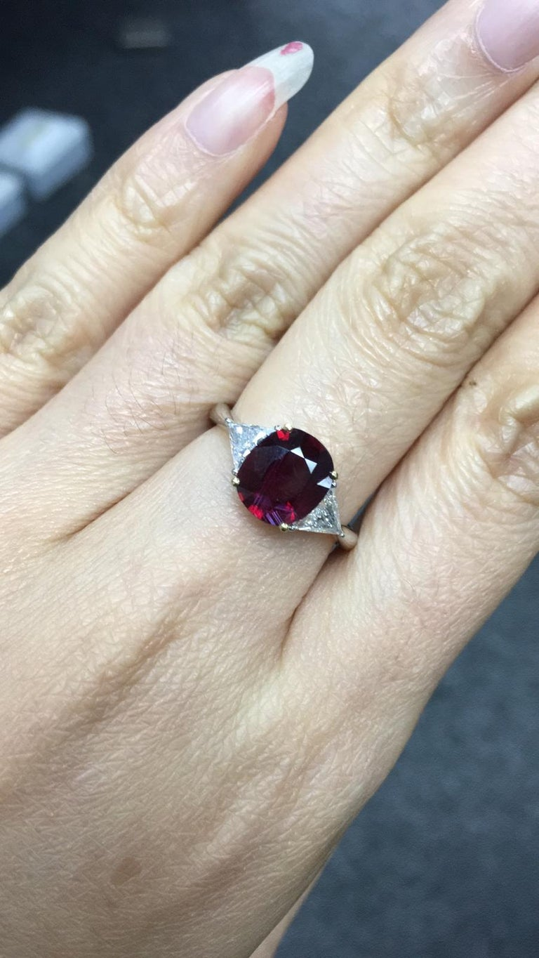 Primary Stone: Ruby (Mozambique) Shape : Cushion Cut Ruby Weight: 2.08 Carats  Measurements Ruby: 8.63mm x 7.48mm x 3.49mm Color: Vivid Red Accent Stones: Genuine Diamond Shape Or Cut Diamond: 2 Triangular Brilliants Average Color/clarity Diamond: