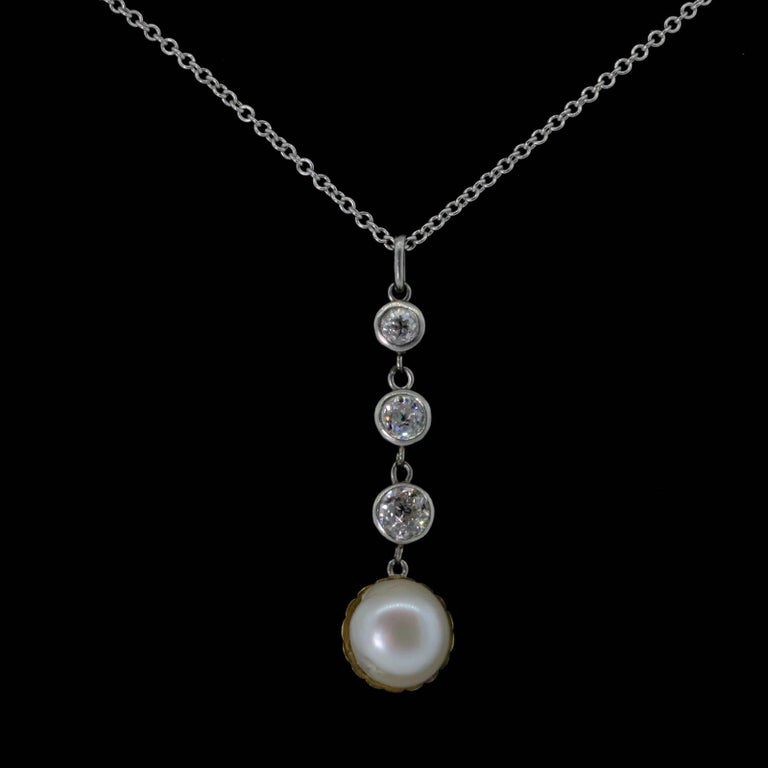A beautiful coveted platinum top, articulated pendant that features three Old Mine Cut Diamonds weighing 0.60 carat; set in 14KT yellow gold bezels.  A dangling layered Natural Pearl is set on a yellow gold clam shell cup.  The beautiful Pearl