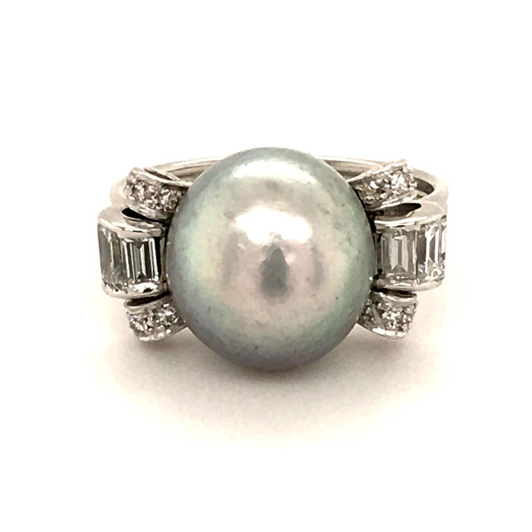 This extraordinary light gray, button-shaped, half drilled Natural Pearl is accompanied with SSEF Report. Measurements: 11.68 -12.54 x 10.67 mm The elegantly curved ring shoulders are set with baguette cut diamonds and single cut diamonds totalling