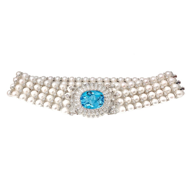 Art Deco, 18 karat white gold, natural pearl, blue topaz and diamond collar necklace and bracelet set. The necklace has an estimated 7.00 carats total weight in diamonds, 20.00 + carat natural blue topaz center and 152 natural pearls. The bracelet