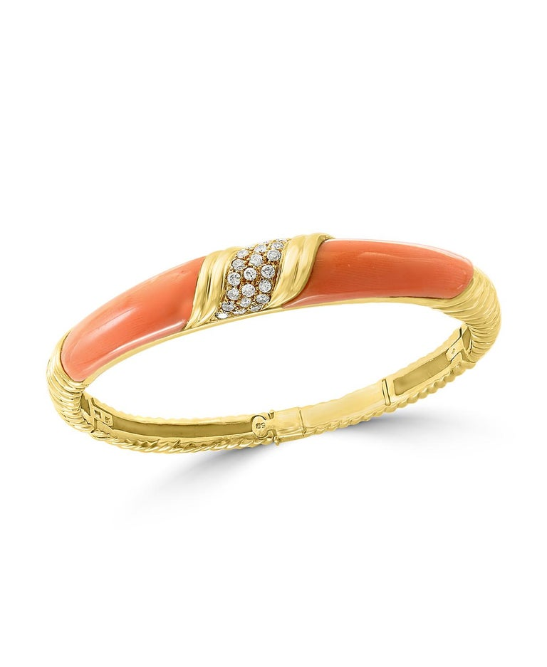 A spectacular jewelry piece.  This exceptional  and very reasonable in price Bangle bracelet   It has two large pieces of natural pink Coral and  approximately  0.80 ct. brilliant diamonds   The  Bangle bracelet is expertly crafted with 23 grams of