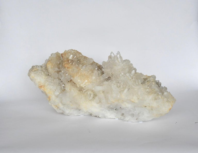 A horizontal natural rock crystal sculpture with peaks and grottoes.