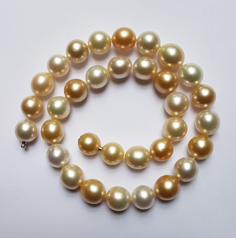 This luxurious and elegant necklace consists of 33 natural south sea pearls of 12-13 mm with high lustre.  The natural colors range from a warm creme to a striking gold.  The clasp is made of a matching pearl in bajonette style. A must to complete