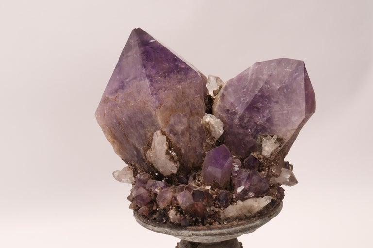 A Naturalia mineral specimen. A Druze of amethyst and quartz crystals mounted over a wooden base on a vase shape, Italy, circa 1880.