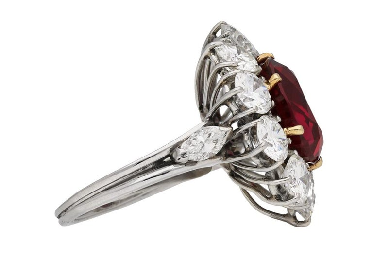 Vintage ruby and diamond coronet cluster ring. Set with a natural unenhanced cushion shape old cut Siam ruby to centre in an open back yellow gold claw setting with an approximate weight of 6.19 carats, encircled by a single row of ten round