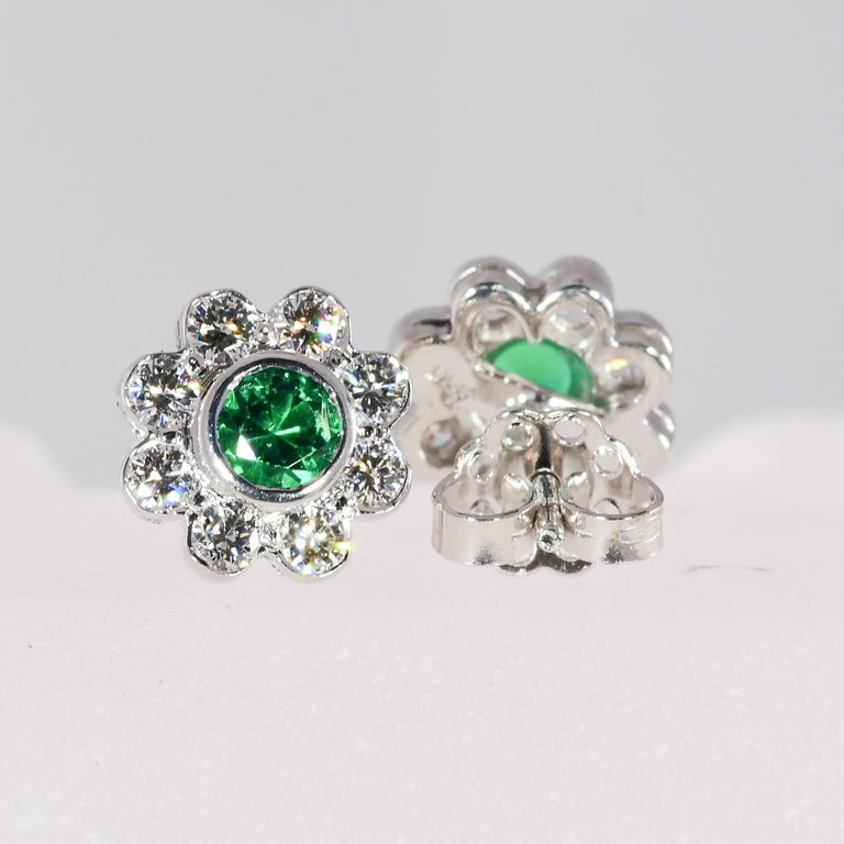 Classic design natural round vivid emeralds totaling .46 carat are encircled by .75 carat total weight of diamonds. The quality of the diamonds range from VVS2-SI1 clarity and G-H color. The bezel set earrings are 18 karat white gold. The weight is