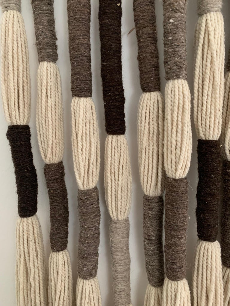 Reminiscent of Jane Knight's wall art in the 1960s, this is made from 100% natural died wools. This oversized wall hanging with earth tones (browns, greys and beige) is all hand made in a Mexican artist colony. The scale and ease of hanging is