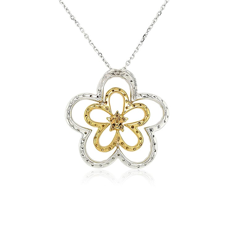 This unique 18K gold pendant features lustrous Yellow diamonds set amongst a floral motif of White diamonds. The diamonds intertwine to create two abstract flowers. A romantic, but striking piece, this beautiful pendant will add an exceptional