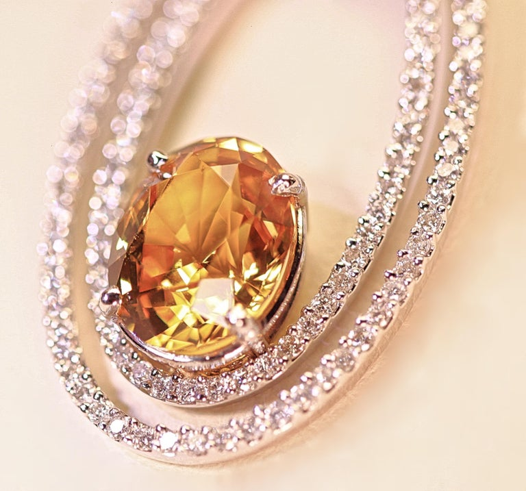 A beautiful natural yellow sapphire enhanced by classy diamond oval circles.  The yellow sapphire has an AGL certificate grading it a natural stone that has not been heat enhanced.  The yellow sapphire weighs 4.05 carats total and the diamonds weigh