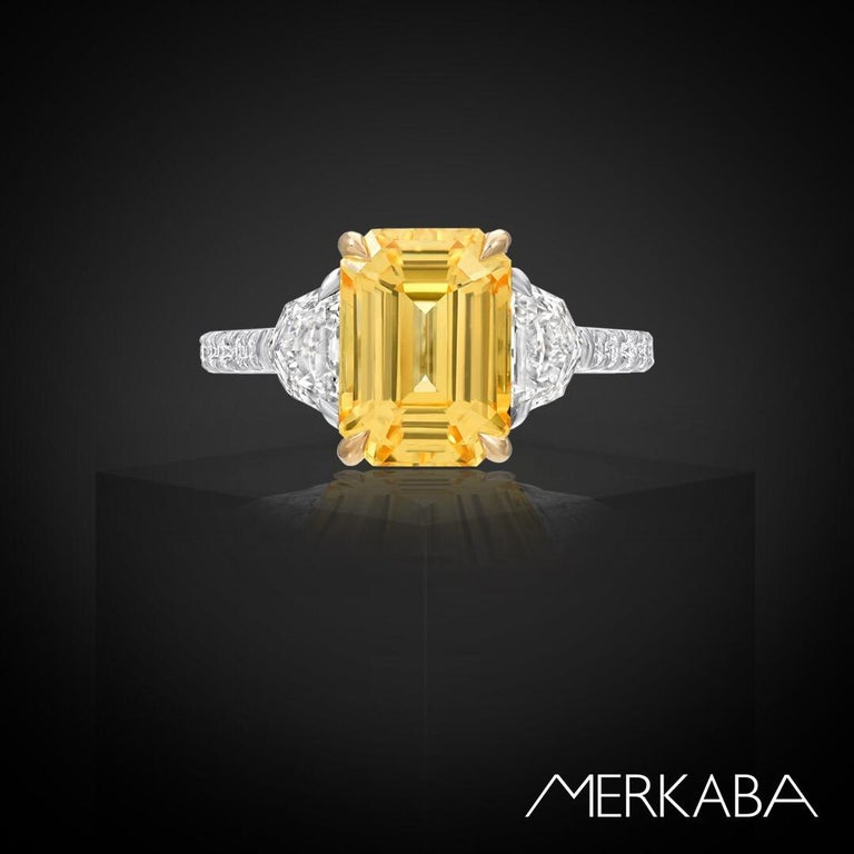 Supreme no heat 4.47 carats Yellow Sapphire emerald cut, flanked by a pair of 0.75 carats total, F/VS2 Epaulet shaped diamonds, and adorned by a total of 0.30 carats of round brilliant diamonds, comprise this platinum and 18K yellow gold,
