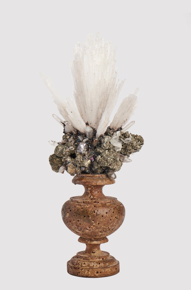 A Naturalia mineral specimen: A composition with Scolecite and pyrite crystals, mounted over a guild-plated wooden base on a vase shape.
