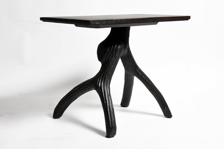 The rectangular top rests on a naturalistic tree branch-form carved table base that is sure to add rustic charm to any space. The table features a new black lacquer finish that was tastefully done and still shows some of its original color through