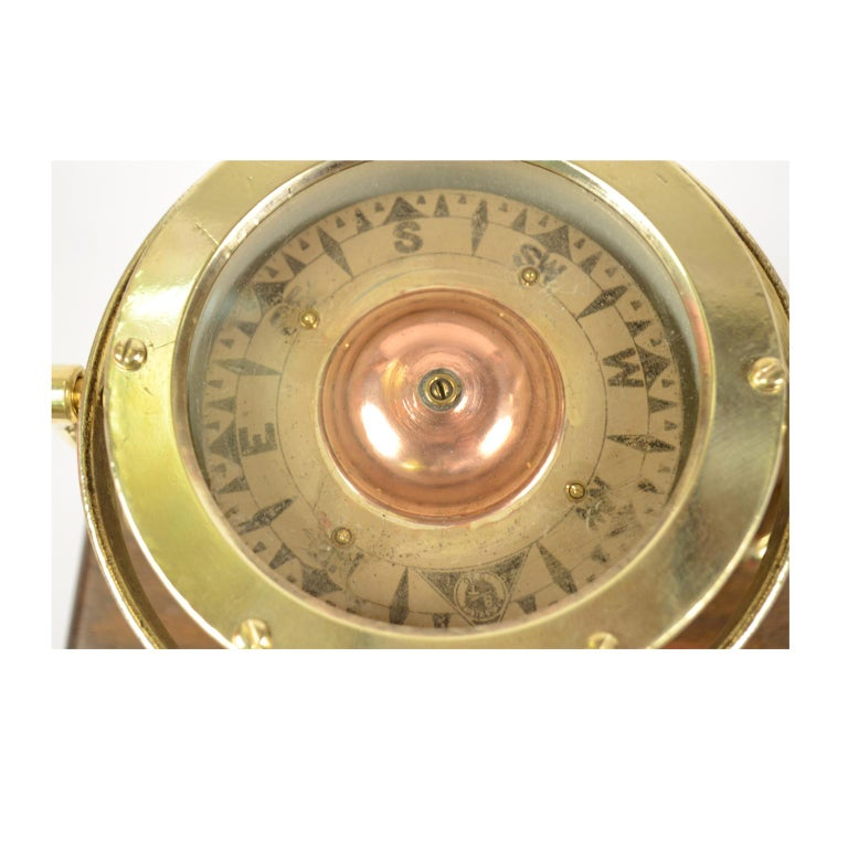 Nautical liquid compass, brass, on universal joint, British manufacture, mounted on wooden board. The compass is signed Sestrel BT 1876 the compass has a cylindrical brass container, on the bottom of which a stem of hard metal is fixed, on which
