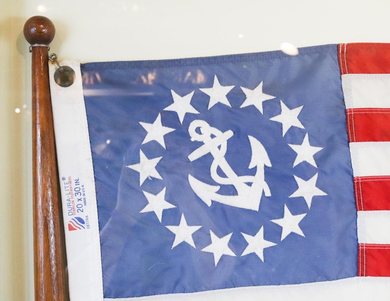 Nautical yacht ensign with pole mounted into a custom shadowbox cabinet. Red, white and blue ensign with embroidered fouled anchor surrounded by thirteen stars. Measures: 35.5
