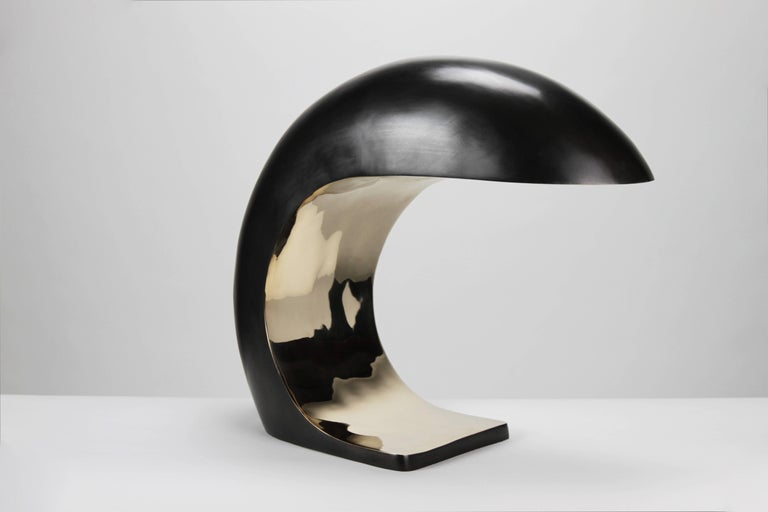 The nautilus lamp is inspired by midcentury Italian design. It is cast bronze and weighs up to 28 pounds. The outer shell has a blackened patina and the face is high polished to a mirrored finish.   The nautilus illuminates by a three-way touch