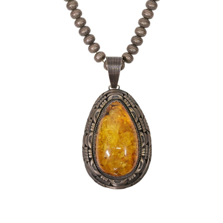 Solid amber pendant necklace. Marked Sterling, signed Charles Johnson. Stunning giant amber, beautiful antique chain, lightweight for the size. Chain is detailed with hand stamped decorated beads.  PERIOD: After 1950  ORIGIN: Navajo,