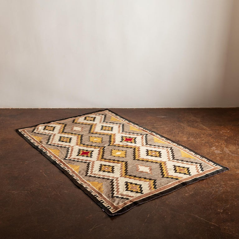 A Classic Navajo eye dazzler textile in ochre, neutrals and a pop of red, 1940s.