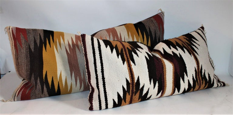 Navajo Indian weaving bolster pillows in fine condition. These were originally saddle blanket weaving's. The backing is in cotton black and brown linen. The inserts are down and feather fill.  Measures: 33 x 17 - Smaller pillow  37 x 18 - Larger