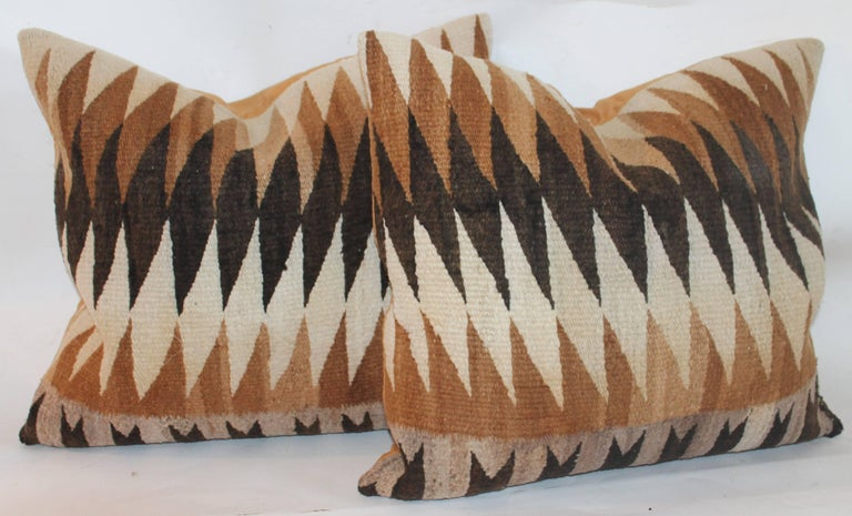 These early eye dazzler Navajo weaving pillows are in fine condition and have mustard cotton linen backings. Sold as a pair only.