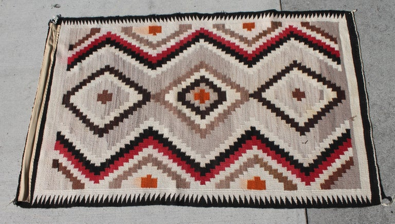 This fine Navajo Indian weaving is in fine condition with a nice mellow fade throughout. The colors are fantastic and pattern is quite nice as well.