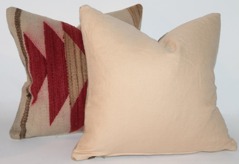 This pair of Navajo Indian weaving pillows are in good condition. The backings are cotton linen and down and feather fill.