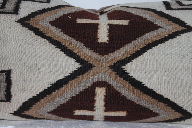 This large Navajo Indian weaving bolster pillow has a leather backing and has crosses for a design pattern. The condition is very good.