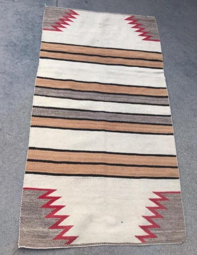 This fine striped Navajo Indian weaving is in good condition with zig zag ends. The weaving has a somewhat overall fade look to it.