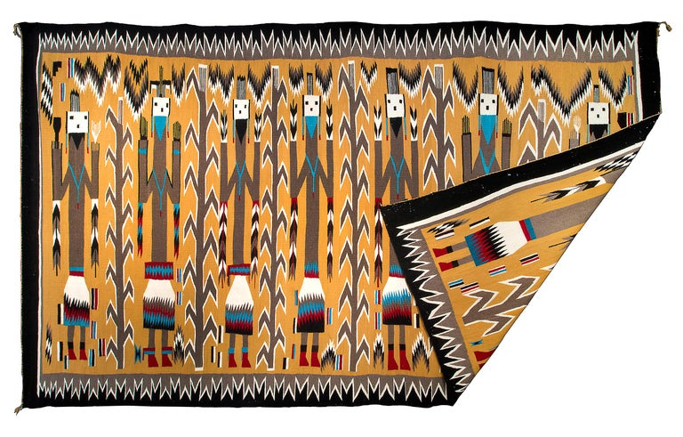 Vintage Navajo area rug, circa 1950s, Pictorial Weaving with seven Yei (Yeibichai) figures holding feathers. Hand-woven by a Navajo weaver in colors of yellow, black, white, blue and red. This southwestern rug is well suited for use on the floor as