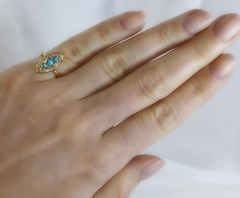 Early 20th Century 18ct Rose gold Marquise design Turquoise and Diamond ring with three  central set Turquoise framed with Old-cut diamonds.  English origin, Early 20th Century. Marquise Approx 17mm Long.