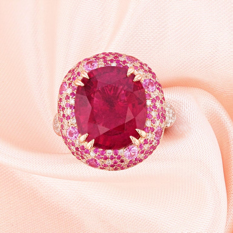 This ring is made in 14k white and rose gold featuring a 7.96ct GIA certified oval cut pink tourmaline. The certificate number is GIA 1162366466. The ring also features 141 pink sapphires pave set on the halo weighing 1.40ct and 96 round cut
