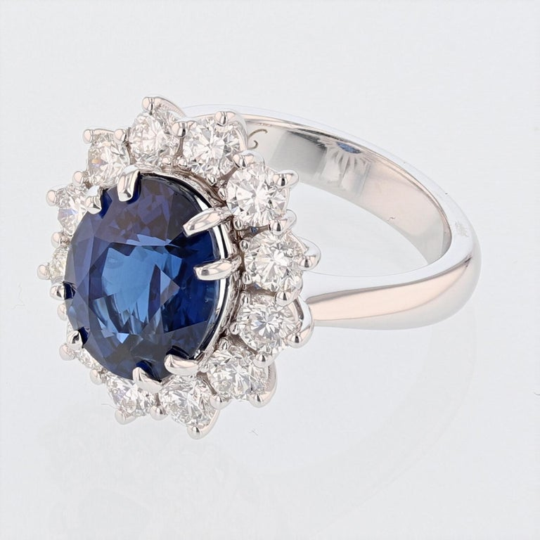 This ring is made in 18k white gold and features a GRS certified, vivid blue, oval cut sapphire weighing 6.46ct. The certificate number is GRS2015-034115. The ring also has a diamond halo featuring 12 round cut diamonds weiging 1.82ct color grade
