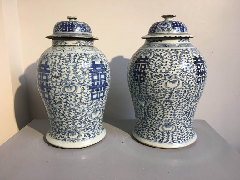 A near pair of Classic Chinese blue and white covered temple jars. The jars of elegant baluster form, painted in rich cobalt blue with large Chinese double happiness characters and intricate scrolling floral and foliate pattern against a white