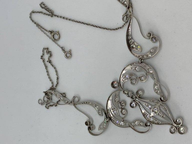 An early 20th Century three-part necklace having stylised heart centre panel between two long scrolls all suspended at the centre of a trace link chain. The wing panels of the necklace contain twenty-six diamonds totalling  .95cts. The centre panel