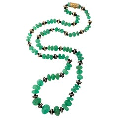Necklace of Graduated Melon Shaped Emerald Beads with Onyx and Diamond Spacers