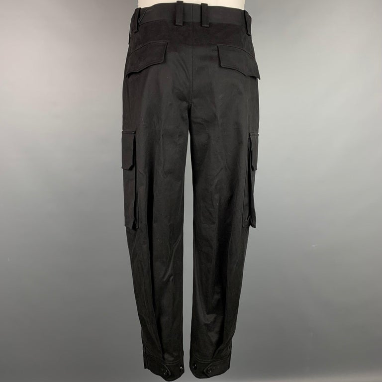 NEIL BARRETT casual pants comes in a black cotton featuring a cargo style, patch pockets, and a zip fly closure. Made in Italy.   New With Tags.  Marked: 46 Original Retail Price: $647.00  Measurements:  Waist: 32 in. Rise: 12 in. Inseam: 28 in.