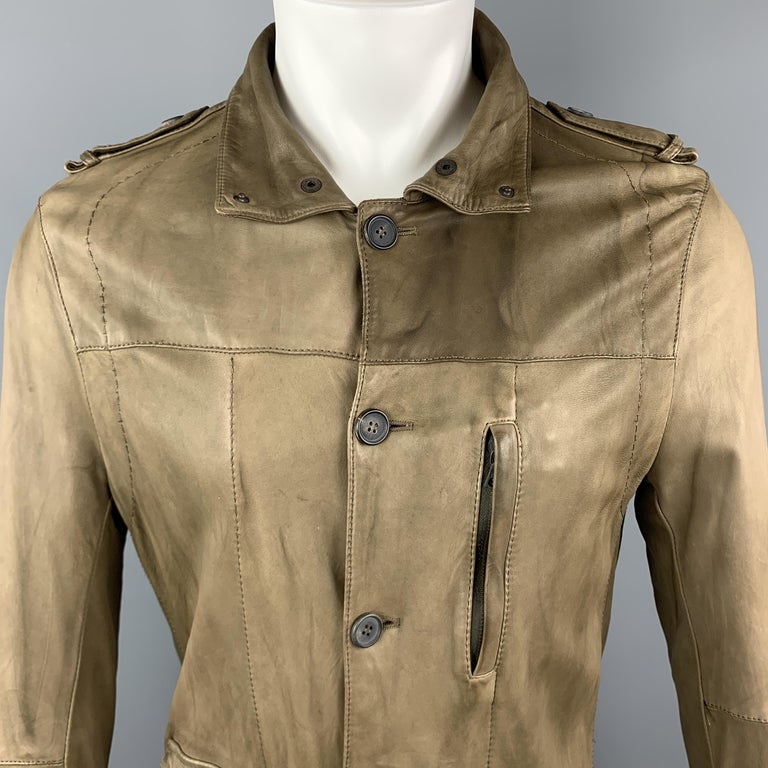 NEIL BARET jacket comes in light weight taupe leather with a folded snap collar, button up front, flap and zip pockets, epaulets, and top stitching. Wear throughout. Made in Italy.  Good Pre-Owned Condition. Marked:  Measurements:  Shoulder: 17
