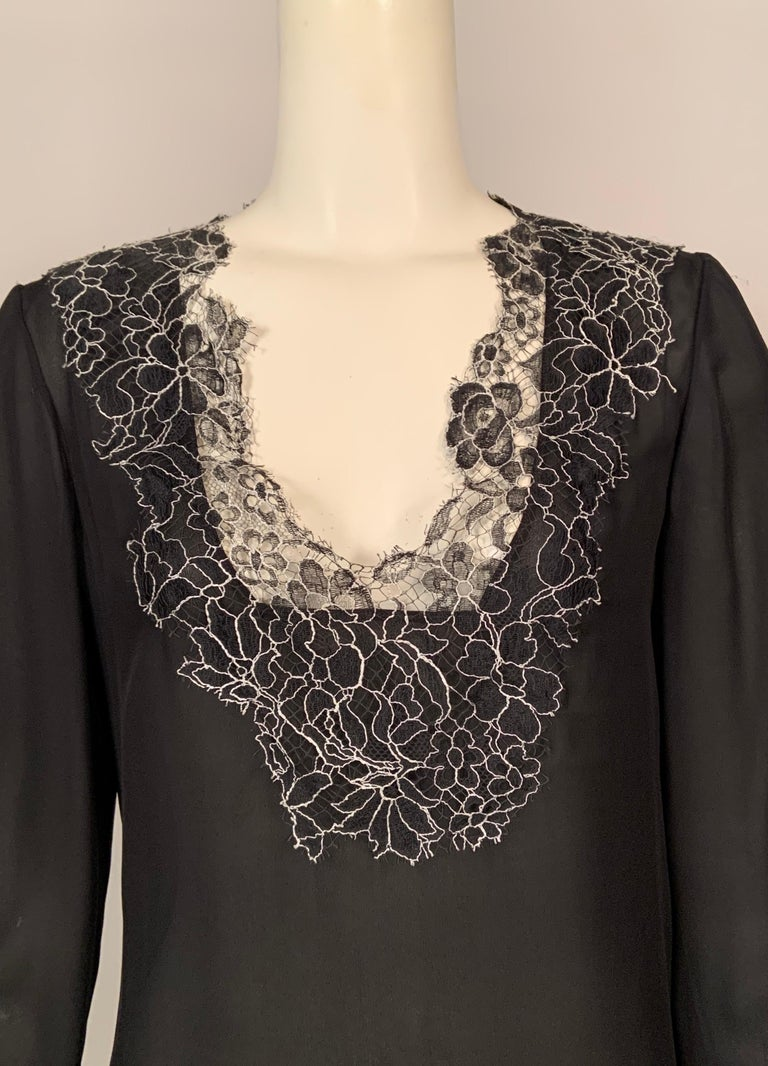 Two layers of semi sheer black silk chiffon are trimmed with a deep border of black and white floral lace, so delicate it resembles a spider web. The blouse was retailed by Neiman Marcus and still bears the original tags. There is a left side zipper