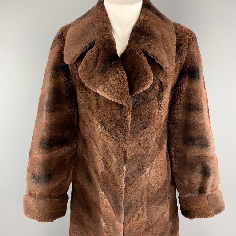 Vintage ZUKI for NEIMAN MARCUS fur coat comes in geometrical placed dyed muskrat fur with a pointed collar lapel, cuffed sleeves, slit pockets, and printed liner. Buttons have been removed. As-is. Made in Canada.   Very Good Pre-Owned