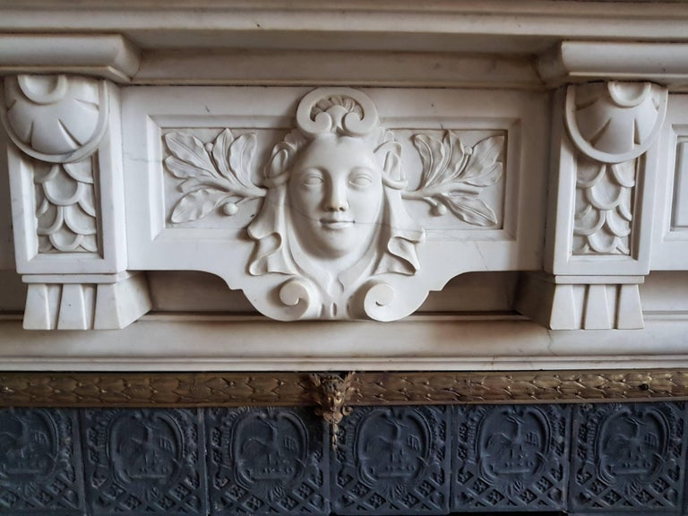 This is a sophisticated, neo-classical fireplace, made of the most soft-toned Carrara marble, named Statuary. The breakfront frieze is centered with an elegant female-head.  This modest mantel is an example of a fireplace that brings a great