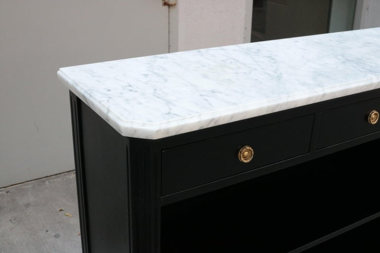 Neoclassical inspired étagère in the style of Jansen. Ebonized fruitwood with patinated brass details and a marble top.