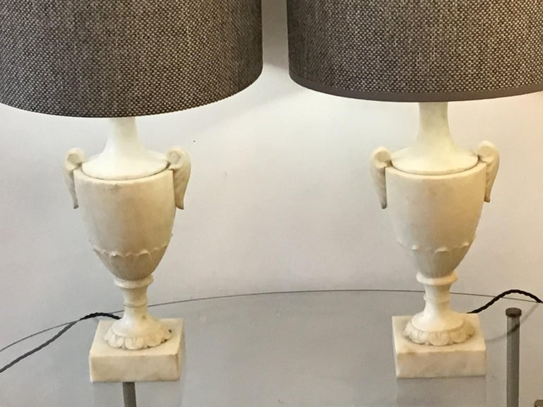 A pair of Italian alabaster lamp created in the early 20th century, The base of this Italian lamp is carved into a Classic shape re wired and tested. Cc Italian.