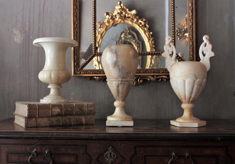 Elegant alabaster urn table lamp with neoclassical design. Spain, 1940-1950s This turned alabaster urn lamp with classical design has carved details on the bottom part. It has a nice color and patina providing a charming light when lit. This