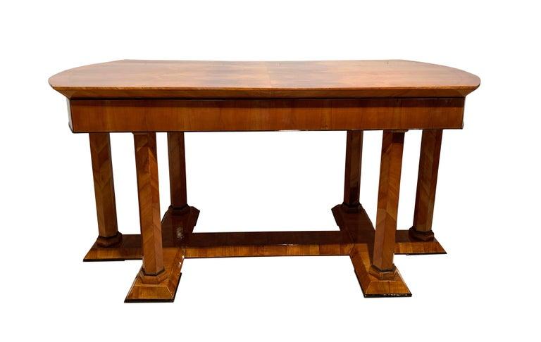 Rare, elegant neoclassical Biedermeier desk from Austria, 19th century, around 1830.  Very beautiful book-matched cherry veneer on softwood. Typical Austrian hexagonal, veneered columns on a veneered pedestal. Ebonized trims. 1 long drawer.