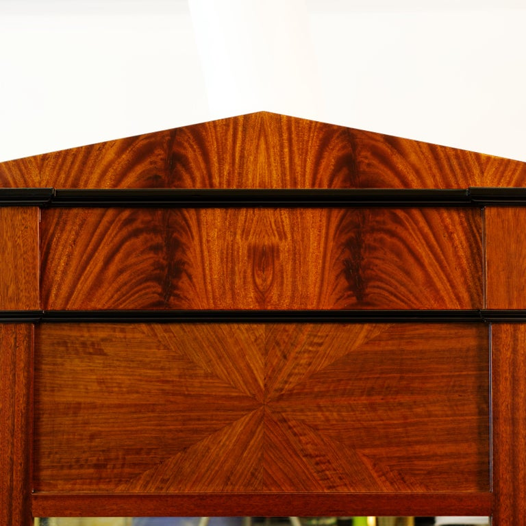 This mirror was inspired by various Biedermeier examples, featuring strong contrasting veneer work and exotic solids. Mahogany frame is accentuated by crotch mahogany veneer. Insert panels are sunburst figured walnut veneer. The mirror is finished