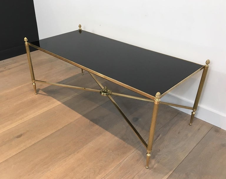 This beautiful neoclassical bronze and brass coffee table has a nice new black lacquered glass top. This cocktail table is French and attributed to Maison Baguès, circa 1940.