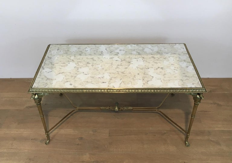 This rare coffee table is made of bronze and brass with a faux-antiques mirror top. It has swan figures on each corner and claw feet. This is a very interesting coffee table, in the style of Maison Jansen. This is French, circa 1940.